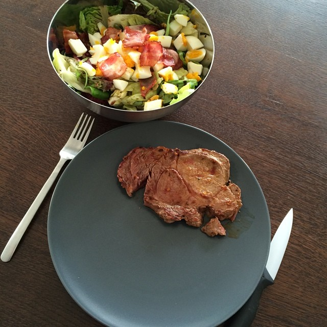 Mixed salad with a beacon / egg topping and a beef steak. Classic after workout meal.